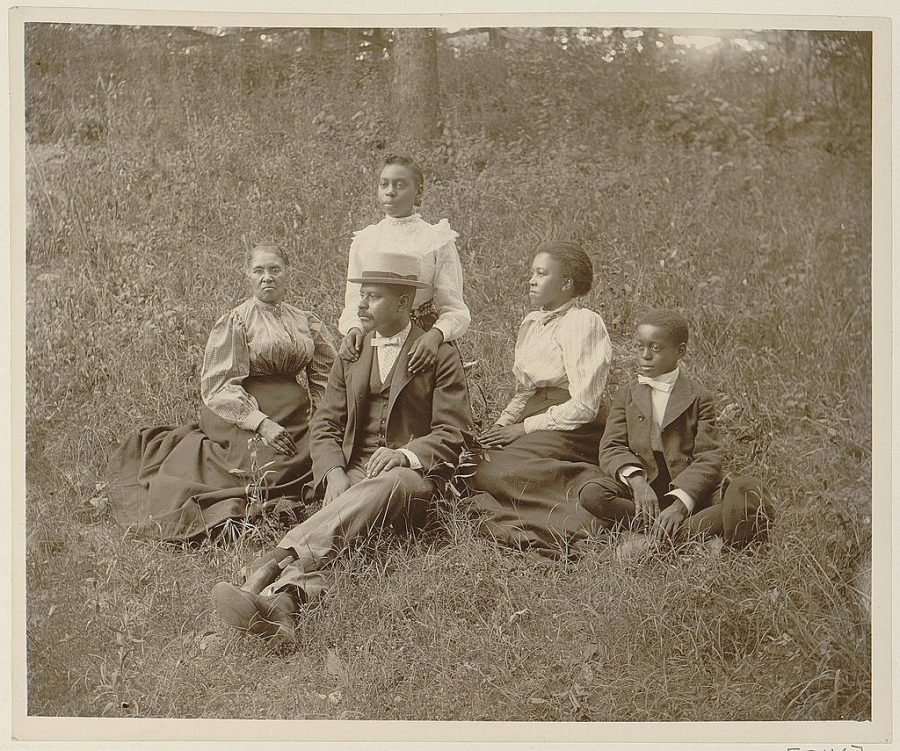 African American family posed for portrait seated on lawn.